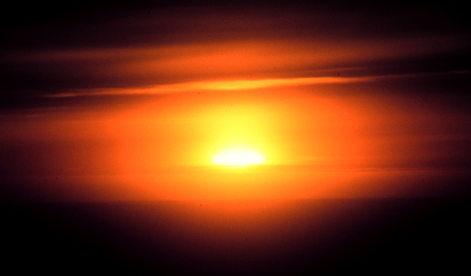 haze_and_clouds_obscure_the_setting_sun_-_noaa